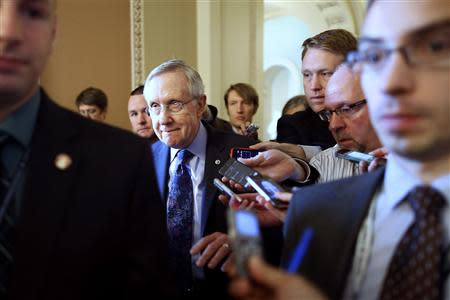 U.S. Senate Majority Leader Reid is trailed by reporters on his way to a Democratic caucus meeting at the U.S. Capitol in Washington