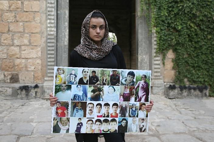 Yazidi woman Ashwaq Haji, allegedly used by the Islamic State group (IS) as a sex slave, holds portraits of jihadists' victims from her village as she visits the Lalish temple, in Lalish, northern Iraq, on August 15, 2018 (AFP Photo/-)