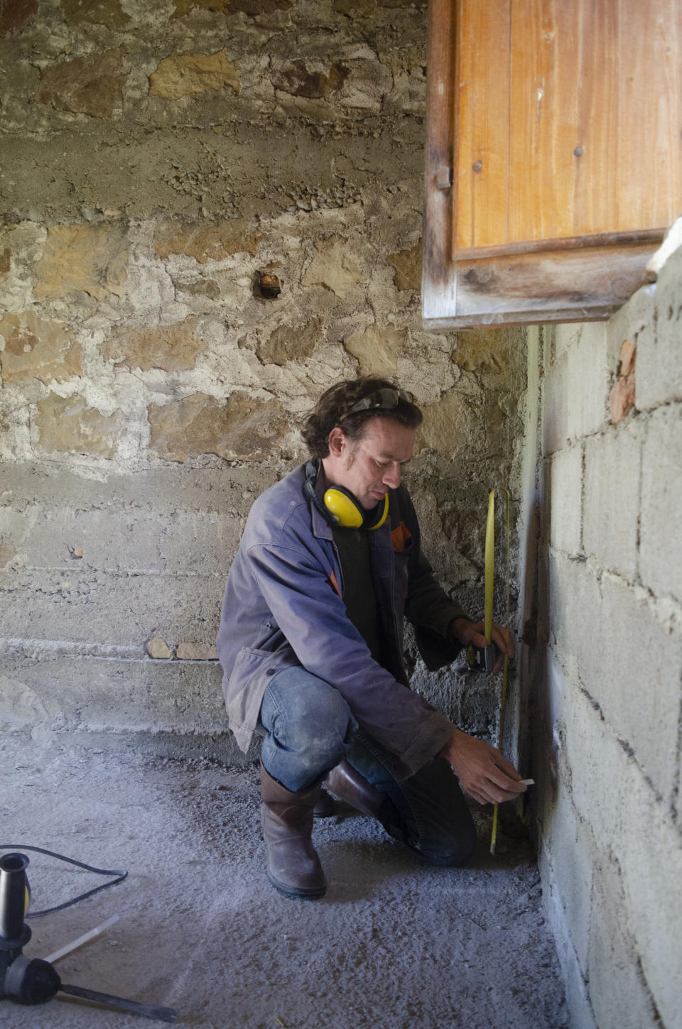 Cain Burdeau marks where he wants to place an electrical outlet on a wall inside a country home he is renovating in Castelbuono, Sicily, on April 8, 2021. (AP Photo/Audrey Rodeman)