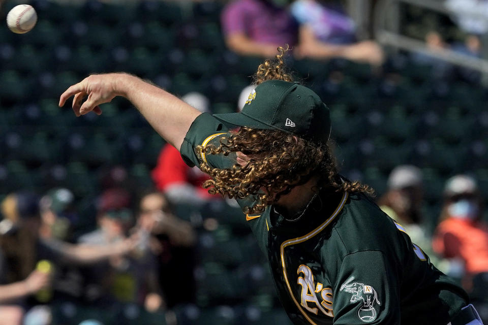Oakland Athletics pitcher Grant Holmes throws against the Cincinnati Reds during the first inning of a spring training baseball game, Monday, March 1, 2021, in Mesa, Ariz. (AP Photo/Matt York)