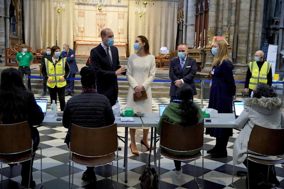 Britain's Prince William, Duke of Cambridge and Britain's Catherine, Duchess of Cambridge speak to staff during a visit to the coronavirus vaccination centre at Westminster Abbey, central London on March 23, 2021, to pay tribute to the efforts of those involved in the Covid-19 vaccine rollout. (Photo by Aaron Chown / POOL / AFP) (Photo by AARON CHOWN/POOL/AFP via Getty Images)