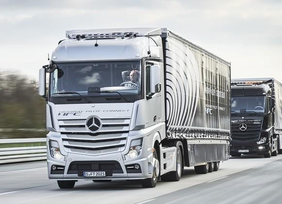 Two Mercedes-Benz tractor-trailer trucks on a highway. The lead truck's human driver has his hands behind his head to show that the trucks are driving themselves.