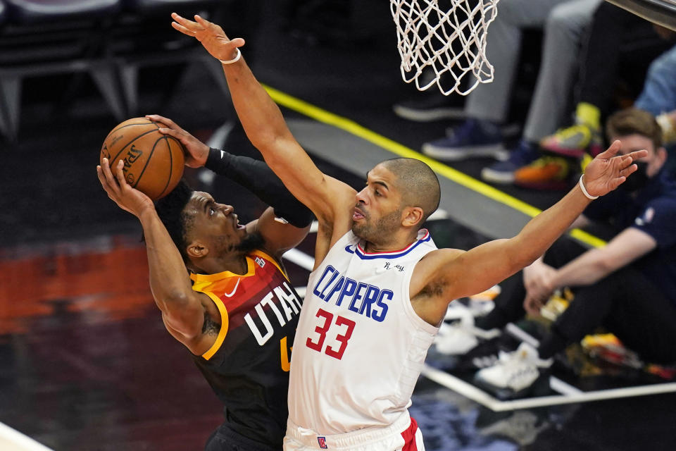 Los Angeles Clippers forward Nicolas Batum (33) defends as Utah Jazz guard Donovan Mitchell, left, goes to the basket during the first half of Game 2 of a second-round NBA basketball playoff series Thursday, June 10, 2021, in Salt Lake City. (AP Photo/Rick Bowmer)