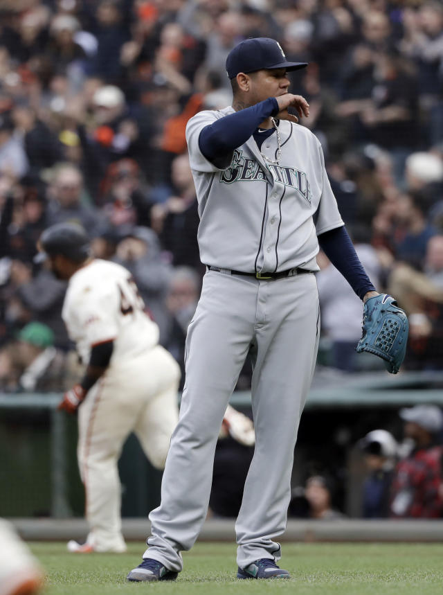 Seattle Mariners starting pitcher Felix Hernandez, right, stands nears the mound after giving up a three-run home run to San Francisco Giants' Pablo Sandoval, rear, during the fifth inning of a baseball game Wednesday, April 4, 2018, in San Francisco. (AP Photo/Marcio Jose Sanchez)