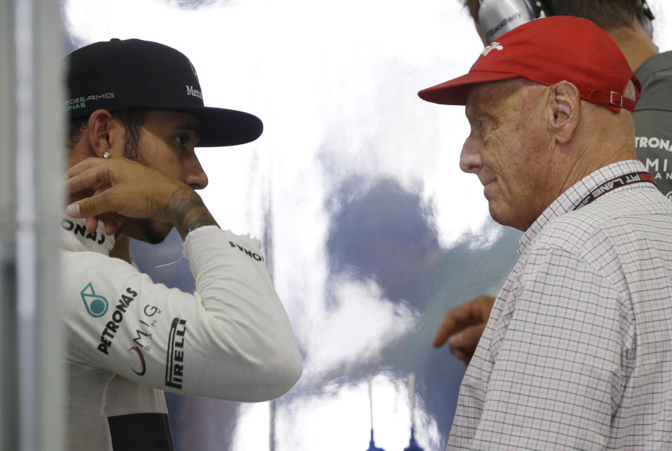 Mercedes driver Lewis Hamilton of Britain, left, talks with former  F1 World Champion Niki Lauda after the first practice session for the Japanese Formula One Grand Prix at the Suzuka Circuit in Suzuka, Japan, Friday, Oct. 11, 2013. (AP Photo/Greg Baker)