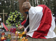 A woman lights a candle at a wooden cross which marks the Soviet-era mass grave site at the Kuropaty during an opposition rally to protest the official presidential election results in Minsk, Belarus, Sunday, Nov. 1, 2020. Nearly three months after Belarus' authoritarian president's re-election to a sixth term in a vote widely seen as rigged, the continuing rallies have cast an unprecedented challenge to his 26-year rule. (AP Photo)