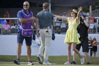 Sam Burns, center, is congratulated by his wife, Caroline Campbell, right, after putting on the 18th green to win the Valspar Championship golf tournament, Sunday, May 2, 2021, in Palm Harbor, Fla. (AP Photo/Phelan M. Ebenhack)