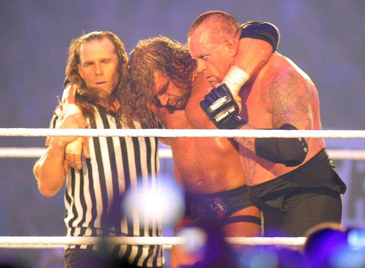 COMMERCIAL IMAGE - In this photograph taken by AP Images for WWE, Hall of famer Shawn Michaels, left, and Undertaker who brings his un-defeated record to 20-0, right, take H.H.H. from the ring during WrestleMania XXVIII in Sun Life Stadium on Sunday, April 1, 2012 in Miami. (Marc Serota/AP Images for WWE)
