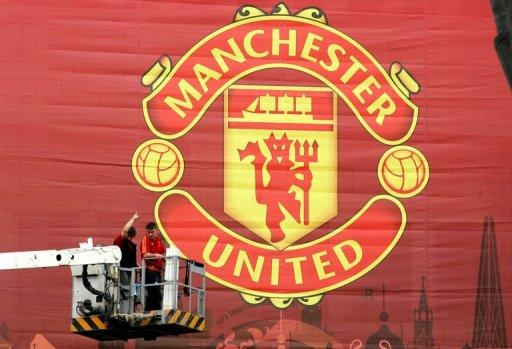 Workmen adjust a large Manchester United banner at Moscow's Luzhniki stadium in 2008. Legendary British football club Manchester United, overloaded with debt since their takeover by a billionaire American family of investors, is moving to raise cash through a US share sale