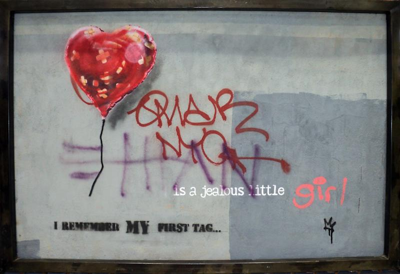 """This undated photo, provided by Keszler Gallery in New York, Tuesday, Feb. 18, 2014, shows """"Bandaged Heart,"""" which was spray-painted on the side of a warehouse in the Brooklyn Borough of New York. Three works by the elusive British street artist Banksy, including two that had to be removed from the sides of buildings, are expected to bring hundreds of thousands of dollars Tuesday night at the Fine Art Auctions Miami. (AP Photo/Richard Drew)"""