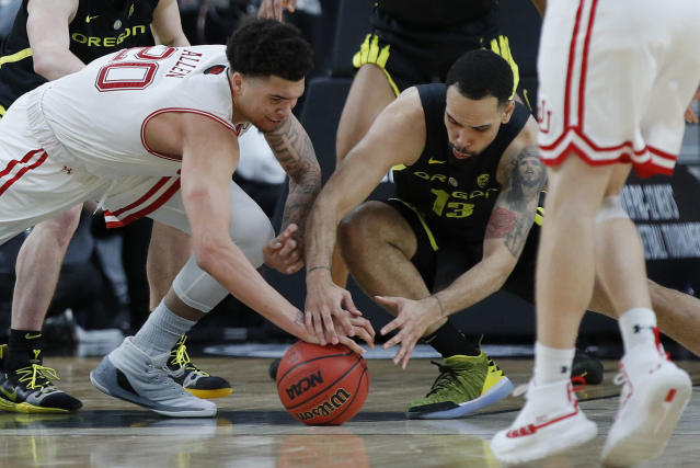 Utah's Timmy Allen, left, and Oregon's Paul White scramble for the ball during the second half of an NCAA college basketball game in the quarterfinals of the Pac-12 men's tournament Thursday, March 14, 2019, in Las Vegas. (AP Photo/John Locher)