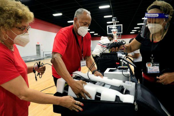 PHOTO: Poll workers Annette Reynolds, Perry Neal and Annette Moses pack up voting machines at an early voting location in Dekalb County for the upcoming presidential elections in Chamblee, Ga., Oct. 9, 2020. (Christopher Aluka Berry/Reuters)