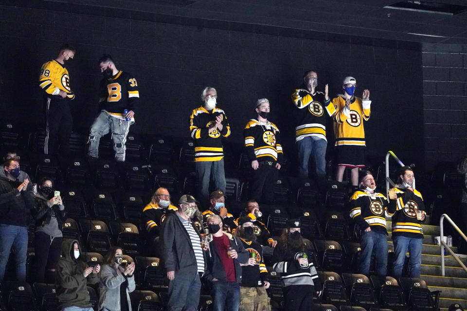Fans cheer during the second period of an NHL hockey game between the Boston Bruins and the New York Islanders at TD Garden, Monday, May 10, 2021, in Boston. Massachusetts has moved to the next step in its COVID-19 reopening plan, allowing large indoor and outdoor venues, including TD Garden, Fenway Park and Gillette Stadium to increase fan capacity from 12% to 25%. (AP Photo/Elise Amendola)