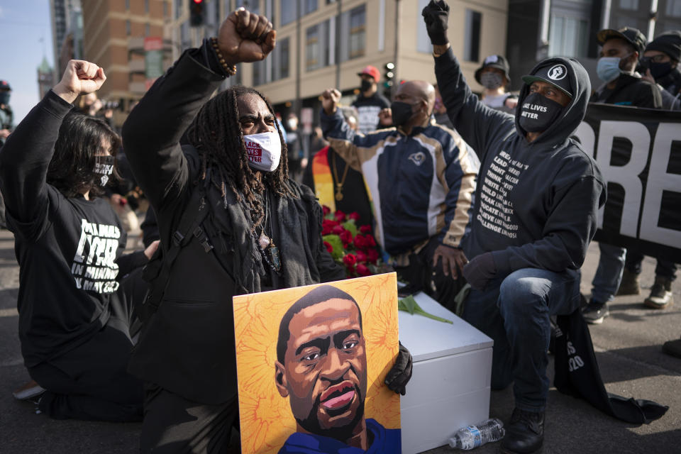 Cortez Rice, left, of Minneapolis, sits with others in the middle of Hennepin Avenue on Sunday, March 7, 2021, in Minneapolis, Minn., to mourn the death of George Floyd a day before jury selection is set to begin in the trial of former Minneapolis officer Derek Chauvin, who is accused of killing Floyd. (Jerry Holt /Star Tribune via AP)