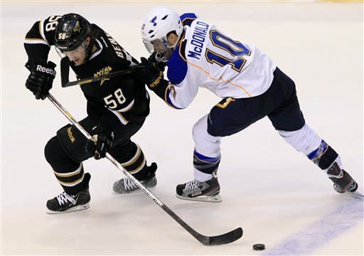Dallas Stars defenseman Jordie Benn (58) passes the puck back as St. Louis Blues center Andy McDonald (10) pressures during the second period of an NHL hockey game on Saturday, Jan. 26, 2013, in Dallas. (AP Photo/John F. Rhodes)