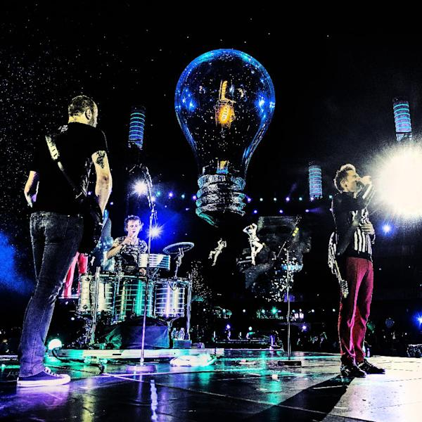 """This photo released by MUSE shows Muse performing in their 4K Ultra High Definition concert film, """"Muse - Live at Rome Olympic Stadium, """" in July 2013. Following advance screenings, the film will be released in over 700 cinemas in 40 countries for limited screenings from Nov. 6, 2013. (AP Photo/MUSE, Hans-Peter van Velthoven)"""