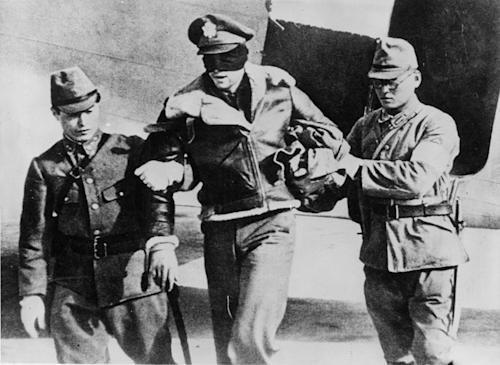 A blindfolded American aviator—perhaps a member of Doolittle's Raiders—is escorted from a plane by Japanese soldiers. The Japanese stated that any airman shot down over Japan during the raid would be executed.