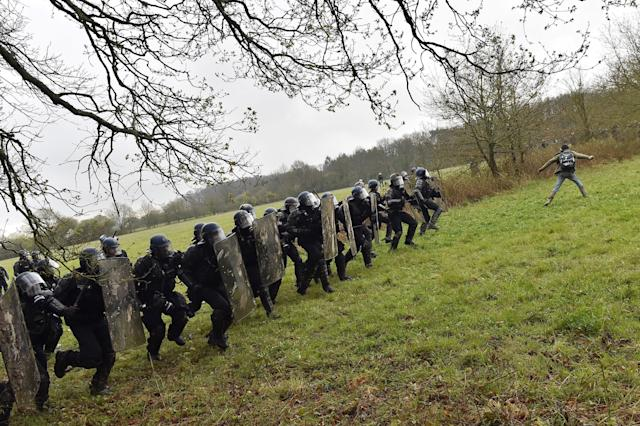 <p>Riot gendarmes charge protesters when clashes erupt on April 10, 2018 during a police operation to raze the decade-old camp known as ZAD (Zone a Defendre – Zone to defend) at Notre-Dame-des-Landes, near the western city of Nantes, and evict the last of the protesters who had refused to leave despite the government agreeing to ditch a proposed airport.<br> (Photo: Loic Venance/AFP/Getty Images) </p>