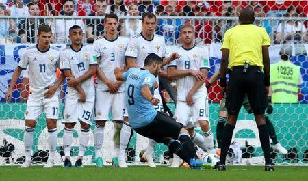 Uruguay's Luis Suarez scores their first goal from a free kick. REUTERS/Pilar Olivares