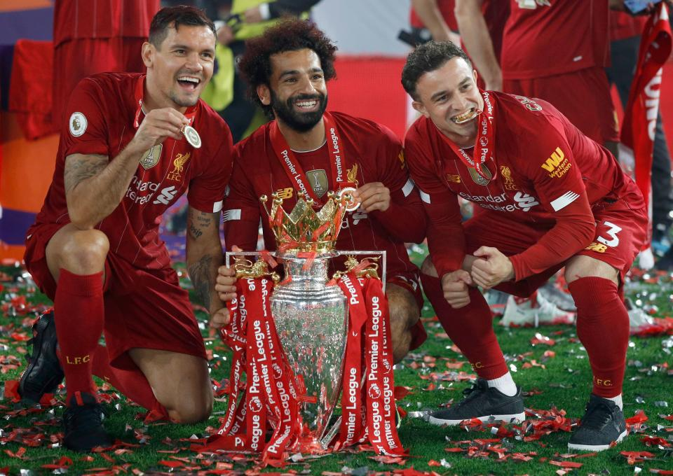 Liverpool's Croatian defender Dejan Lovren (L), Liverpool's Egyptian midfielder Mohamed Salah (C) and Liverpool's Swiss midfielder Xherdan Shaqiri (R) pose with the Premier League trophy during the presentation following the English Premier League football match between Liverpool and Chelsea at Anfield in Liverpool, north west England on July 22, 2020. - Liverpool on Wednesday lifted the Premier League trophy at the famous Kop stand at Anfield after their final home game of the season. With no fans able to attend due to the COVID-19 coronavirus pandemic, Liverpool said the idea for the trophy lift was to honour the club's fans, but Liverpool manager Jurgen Klopp urged fans to respect social distancing measures, after thousands gathered around the club's stadium and in the city centre following their coronation as champions last month. (Photo by PHIL NOBLE / POOL / AFP) / RESTRICTED TO EDITORIAL USE. No use with unauthorized audio, video, data, fixture lists, club/league logos or 'live' services. Online in-match use limited to 120 images. An additional 40 images may be used in extra time. No video emulation. Social media in-match use limited to 120 images. An additional 40 images may be used in extra time. No use in betting publications, games or single club/league/player publications. /  (Photo by PHIL NOBLE/POOL/AFP via Getty Images)