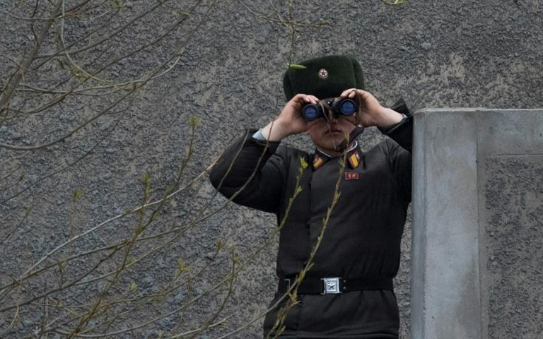 A North Korean soldier gazes across the Yalu border river near Sinuiju, opposite the Chinese city of Dandong, on April 14, 2017