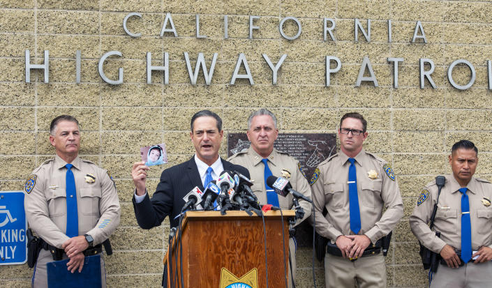 Orange County District Attorney Todd Spitzer holds up a photo of Aiden Leos during a news conference outside the CHP office in Santa Ana, Calif. on Monday, June 7, 2021 to update on the investigation into the shooting death of 6-year-old Aiden Leos. Officials should detail how they tied two suspects, a boyfriend and girlfriend from Costa Mesa, to the shooting. Marcus Anthony Eriz, 24, and Wynne Lee, 23, were arrested Sunday, June 6. (Leonard Ortiz/The Orange County Register via AP)