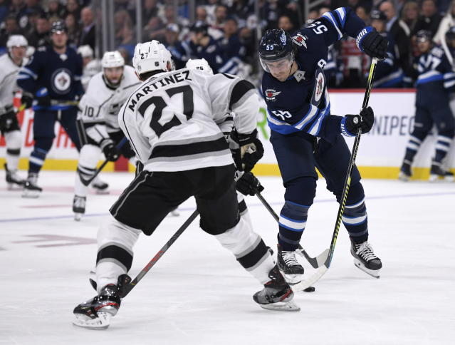 Winnipeg Jets' Mark Scheifele (55) carries the puck past Los Angeles Kings' Alec Martinez (27) during the second period of an NHL hockey game Tuesday, Oct. 22, 2019, in Winnipeg, Manitoba. (Fred Greenslade/The Canadian Press via AP)
