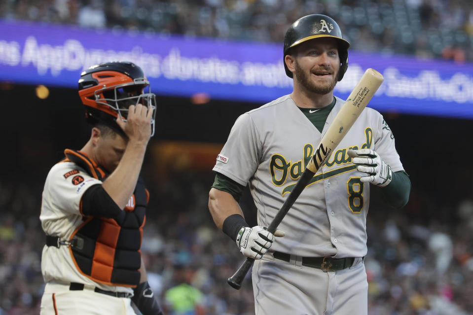 Oakland Athletics' Robbie Grossman, right, reacts after striking out, next to San Francisco Giants catcher Buster Posey during the third inning of a baseball game in San Francisco, Tuesday, Aug. 13, 2019. (AP Photo/Jeff Chiu)