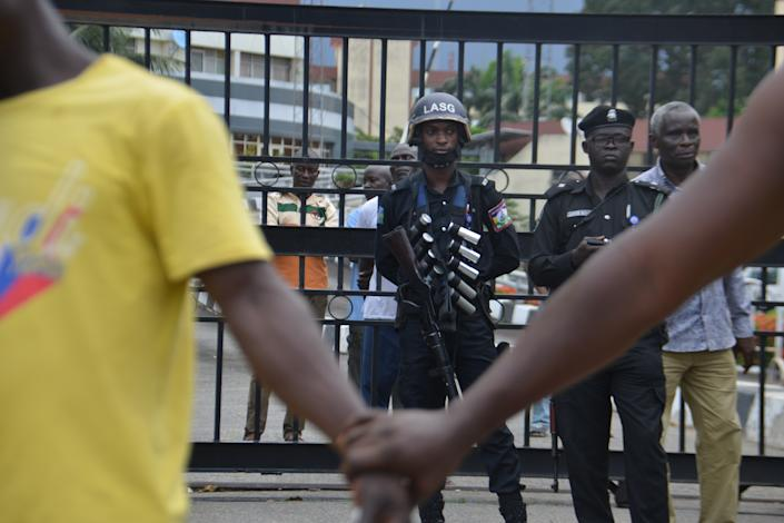 Protesters hold hands to barricade the protesters from the men of the Nigerian Police force. (Photo by Olukayode Jaiyeola/NurPhoto via Getty Images)