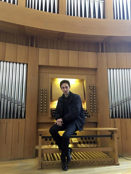 """Vincent Dubois, organist at the Great Organ of Notre-Dame de Paris, poses at the organ at Strasbourg Conservatoire (music school), eastern France, Wednesday April 17, 2019. Dubois, who wasn't in the cathedral, says the instrument """"must be completely dusted off, cleaned from the soot, the dust that is inside."""" (AP Photo/Sylvain Plazy)"""