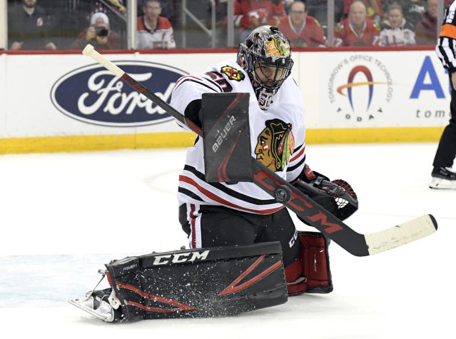 Chicago Blackhawks goaltender Corey Crawford (50) deflects the puck during the second period of an NHL hockey game against the New Jersey Devils, Friday, Dec. 6, 2019, in Newark, N.J. (AP Photo/Bill Kostroun)