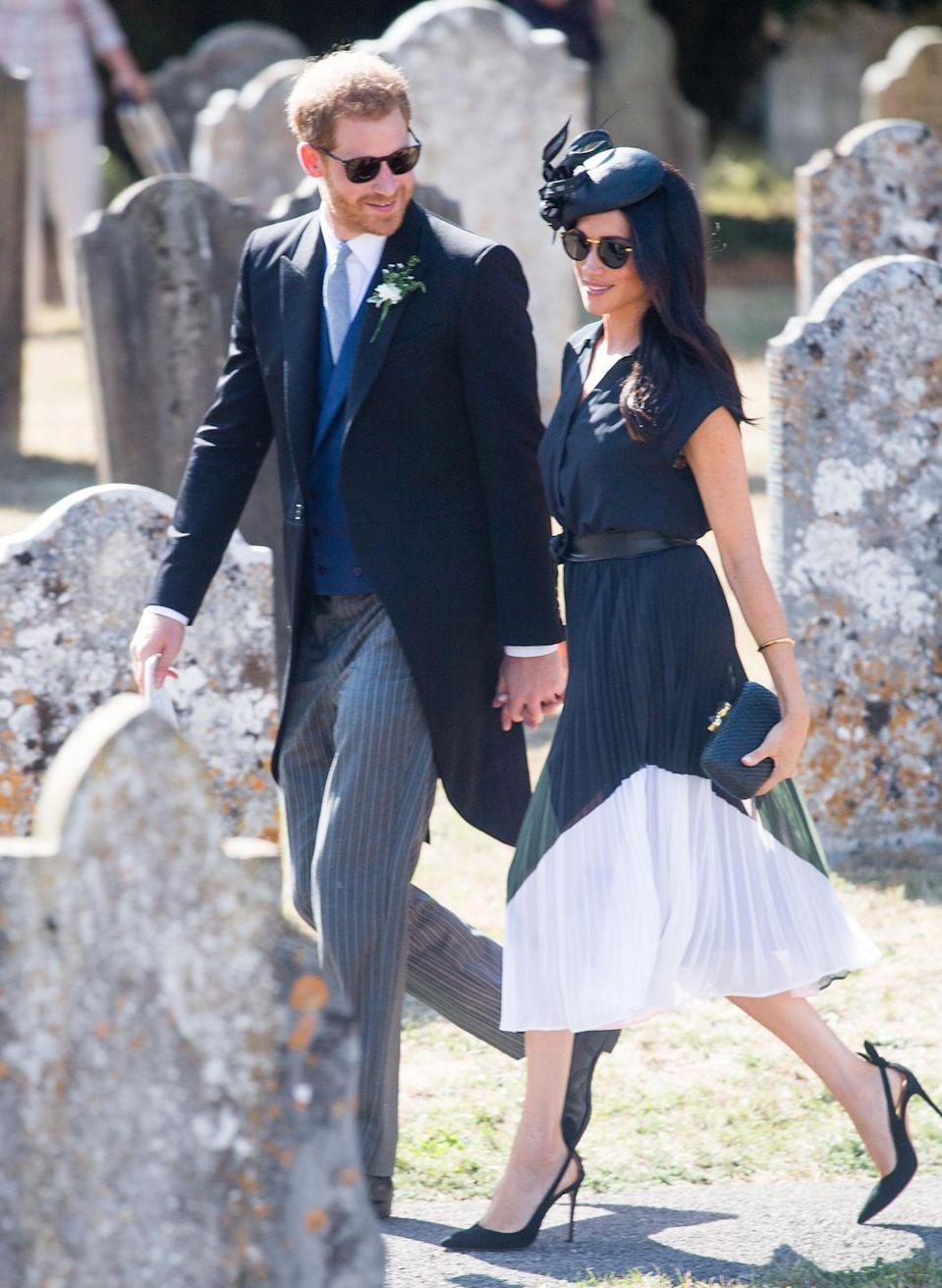 """<p>For their friends <a href=""""https://www.elle.com/uk/life-and-culture/a22648906/meghan-markle-prince-harry-charlie-van-straubenzee-wedding-black-dress/"""" rel=""""nofollow noopener"""" target=""""_blank"""" data-ylk=""""slk:Charlie and Daisy Van Straubenzee's wedding"""" class=""""link rapid-noclick-resp"""">Charlie and Daisy Van Straubenzee's wedding</a>, the newlyweds walked hand-in-hand wearing matching sunglasses, August 2018. </p>"""