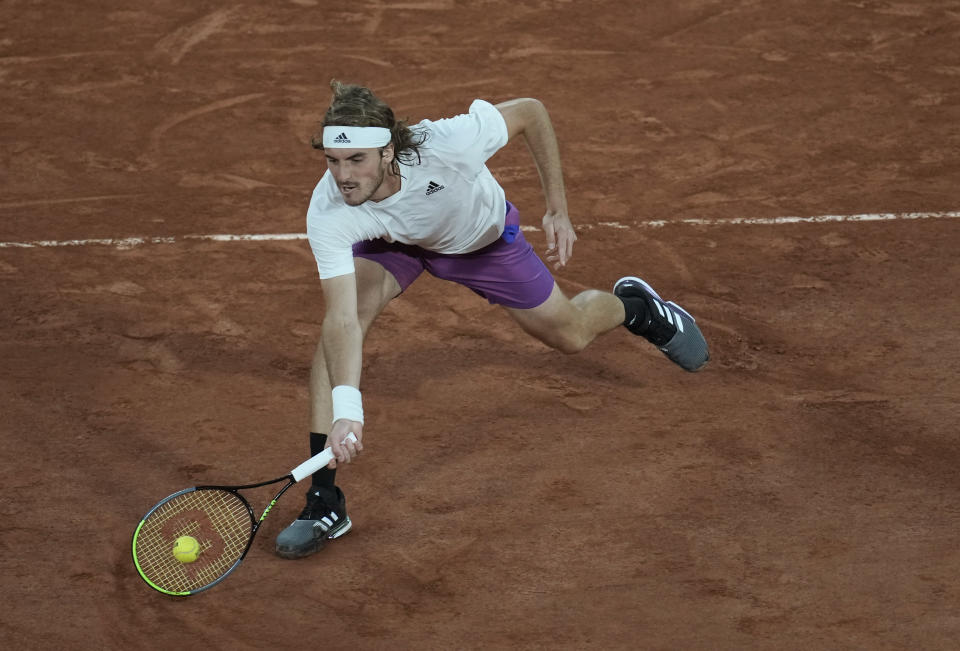 Stefanos Tsitsipas of Greece plays a return to United States' John Isner during their third round match on day 6, of the French Open tennis tournament at Roland Garros in Paris, France, Friday, June 4, 2021. (AP Photo/Christophe Ena)