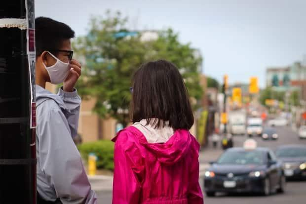 A young man and woman wait for the lights to cross at the intersection of Montreal and North River roads in Ottawa on May 28. (Trevor Pritchard/CBC - image credit)