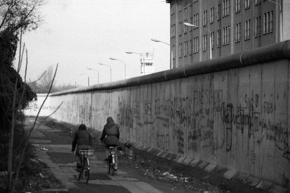 <p>Dos personas en bicicleta junto al muro de Berlín. (Photo by Jürgen Ritter/ullstein bild via Getty Images)</p>