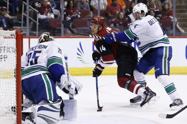 Arizona Coyotes right wing Richard Panik (14) is unable to get a shot off as he gets checked by Vancouver Canucks defenseman Michael Del Zotto (4) as Canucks goaltender Jacob Markstrom (25) waits for the possible shot during the second period of an NHL hockey team Sunday, March 11, 2018, in Glendale, Ariz. (AP Photo/Ross D. Franklin)