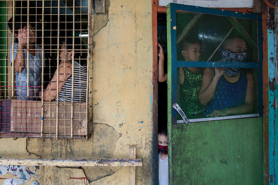 Residents look out from their homes amid the reimposed lockdown to curb the coronavirus disease (COVID-19) cases, in Navotas, Metro Manila, Philippines, August 6, 2020. REUTERS/Eloisa Lopez