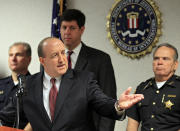 FBI Special Agent in Charge Stephen Anthony points to a map of an attempted bridge bombing at the bureau's office in Cleveland Tuesday, May 1, 2012. Five men, pictured on the wall behind the map, have been arrested for conspiring to blow up the high level bridge over the Cuyahoga River valley. A Justice department official says the five men are self-described anarchists and are not tied to international terrorism. (AP Photo/Mark Duncan)