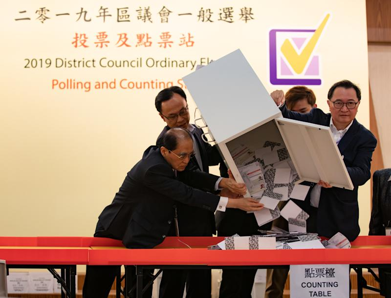HONG KONG, CHINA - 2019/11/24: The Chairman of the HKSAR Electoral Affairs Commission (EAC), Barnabas Fung (second from the right) pours down the ballots from a ballot box to be counted at a polling station. Nearly 3 million Hong Kong citizens cast their ballots on Sundays district council elections in the referendum race between the pro-democracy camp and pro-Beijing camp after more than five months of turmoil in the city. The turnout was confirmed with at least 71.2% of 4.1 million registered to vote. (Photo by May James/SOPA Images/LightRocket via Getty Images)