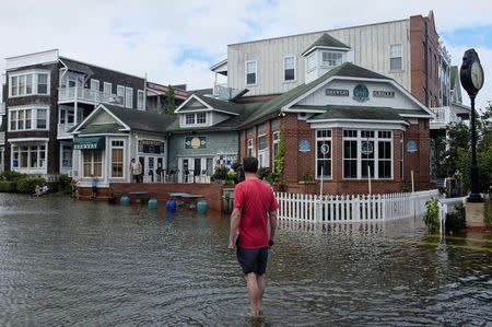 A man walks through a flooded street after Hurricane Arthur passed through in Manteo, North Carolina July 4, 2014. REUTERS/Chris Keane