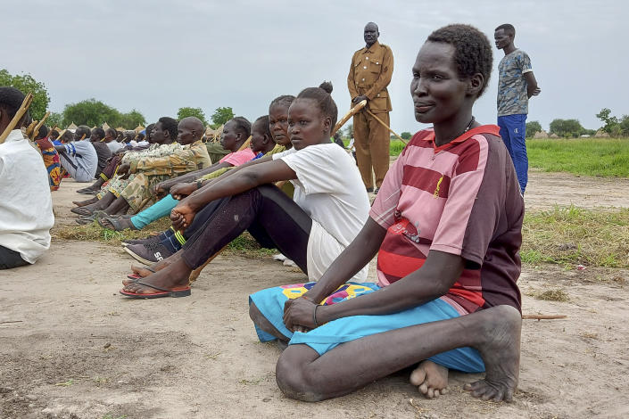 A pregnant police trainee sits with other trainees during the visit of the defense minister to a police training center in Kaljak, South Sudan Saturday, July 11, 2020. At crowded camps in South Sudan, former enemies are meant to be joining forces and training as a unified security force after a five-year civil war so they can help the shattered country recover but they can barely find enough food. (AP Photo/Maura Ajak)