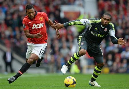 Manchester United's Nani challenged by Stoke City's Palacios during English Premier League soccer match at Old Trafford Stadium in Manchester