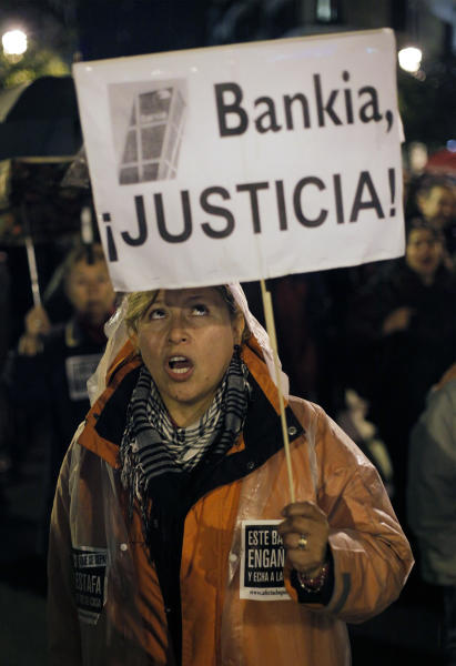 """A woman holds a banner that reads: """"Bankia, Justice!"""" as she shouts slogans against the banks during a march against evictions, in Madrid, Friday, Nov. 9, 2012. Officials say a woman fell to her death as bailiffs approached to evict her for non-payment of the mortgage from her fourth-floor apartment in a suburb of the northern Spanish city of Bilbao. Amaia Egana, 53-year-old, who worked at a local bus depot, was married to a former town councilor and had a 21-year-old daughter, launched herself off her balcony Friday, the regional Interior Ministry said. (AP Photo/Andres Kudacki)"""