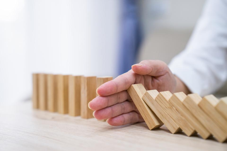 Stopping the domino effect concept for business solution, strategy and successful intervention. Photo: Getty
