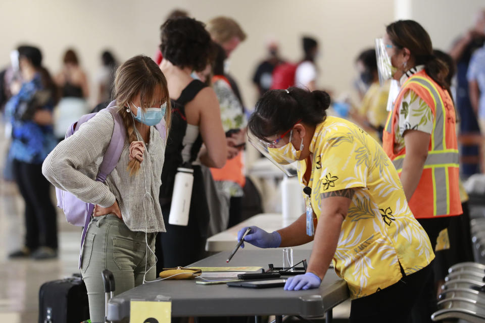 A traveler is assisted by a state official at the Daniel K. Inouye International Airport Thursday, Oct. 15, 2020, in Honolulu. A new pre-travel testing program will allow visitors who test negative for COVID-19 to come to Hawaii and avoid two weeks of mandatory quarantine goes into effect Thursday. The pandemic has caused a devastating downturn on Hawaii's tourism-based economy. Coronavirus weary residents and struggling business owners in Hawaii will be watching closely as tourists begin to return to the islands. (AP Photo/Marco Garcia)
