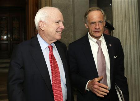 Senators John McCain (R-AZ) (L) and Thomas Carper (D-DE) talk outside of the Senate chamber after voting on the U.S. budget bill in Washington December 18, 2013. REUTERS/Gary Cameron