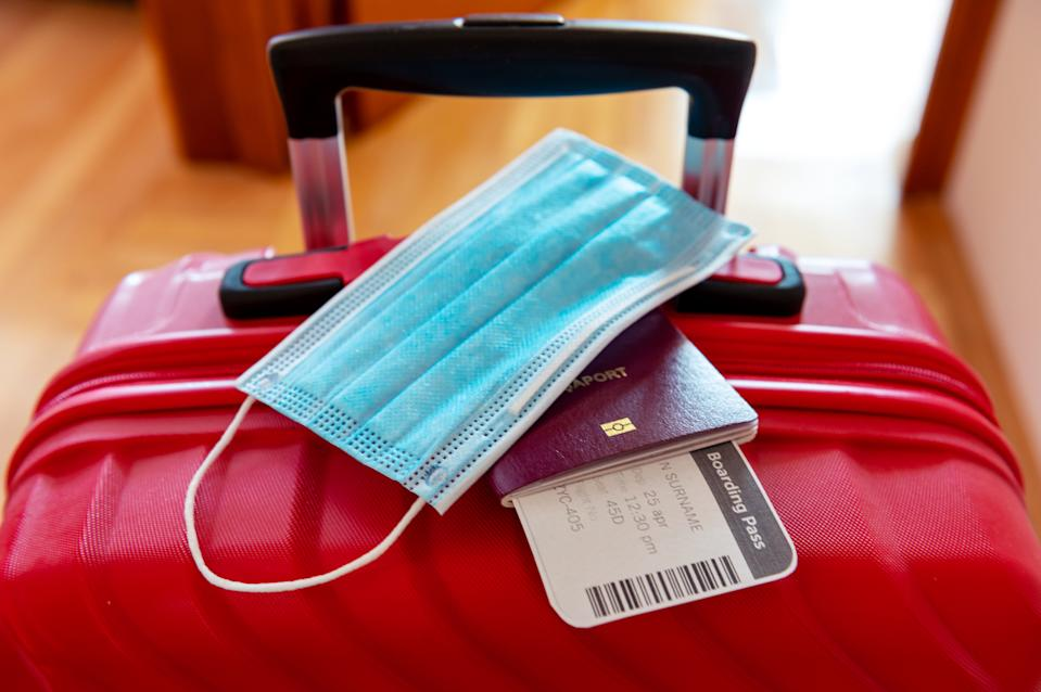 Face protection mask and travel documents over trolley bag. Travel and flight rules during coronavirus pandemic crisis in Europe and world