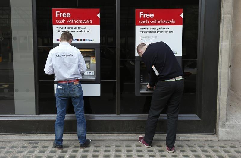 Two men use automated teller machines outside a HSBC bank in London