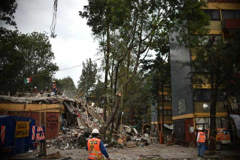 Mexican firefighters remove the debris from a multi-family building that collapsed during the 7.1-magnitude earthquake in Mexico City