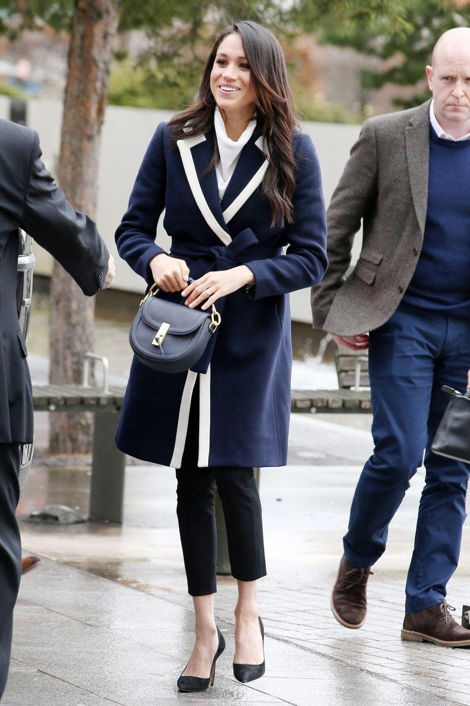 """<p>For her trip to Birmingham on International Women's Day, Meghan wore a now sold-out <a href=""""https://www.net-a-porter.com/gb/en/product/975199?cm_mmc=LinkshareUK-_-TnL5HPStwNw-_-LinkshareUS-_-J84DHJLQkR4-_-Custom-_-LinkBuilder&siteID=J84DHJLQkR4-kqHF2aEzqZnHsdu6c4jWew&siteID=TnL5HPStwNw-tAkWsoNqKZ4aOERaLrj7bg&ShopStyle+%28POPSUGAR%29=ShopStyle+%28POPSUGAR%29&Skimlinks.com=Skimlinks.com"""" rel=""""nofollow noopener"""" target=""""_blank"""" data-ylk=""""slk:two-tone J Crew coat"""" class=""""link rapid-noclick-resp"""">two-tone J Crew coat</a> (similar available <a href=""""https://www.beulahlondon.com/product/chiara-navy-coat/"""" rel=""""nofollow noopener"""" target=""""_blank"""" data-ylk=""""slk:here"""" class=""""link rapid-noclick-resp"""">here</a>) over her white AllSaints Ridley jumper (similar available <a href=""""https://www.allsaints.com/women/knitwear/allsaints-jones-jumper/?colour=4068&category=26"""" rel=""""nofollow noopener"""" target=""""_blank"""" data-ylk=""""slk:here"""" class=""""link rapid-noclick-resp"""">here</a>) - a subtle nod to the colour the suffragettes wore in the early 20th century as they fought for the right to vote, perhaps?</p>"""